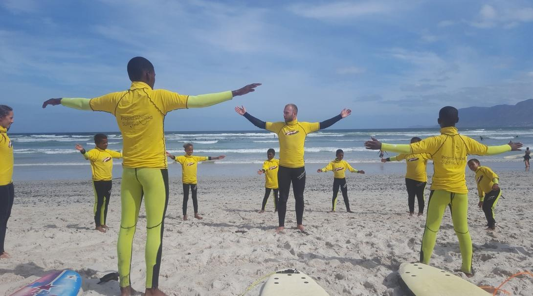 Global Gap volunteers teach children surfing techniques before going into the water at a beach in South Africa.